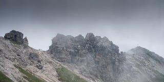 Peak of Großer Daumen with cross in dark clouds in the sky Royalty Free Stock Photo