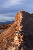 A peak in moon valley in the atacama desert (driest desert on earth) is bathed in the light of the setting sun in front of a storm. Y sky Stock Photos