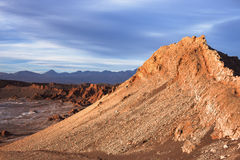 A peak in moon valley in the atacama desert (driest desert on earth) is bathed in the light of the setting sun in front of a storm. Y sky Stock Images