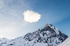 Peak of Mount Machapuchare or popularly known as Fish Tail with a piece of cloud over it as viewed from Annapurna Base Camp, Nepal.  Stock Photo