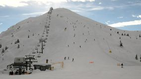 Peak of mountain in ski resort with running rope way. Bunch of skiers on the slope. stock video