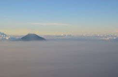 Peak of mountain visible above the clouds during sunset Royalty Free Stock Images