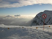 Peak of mountains in ski resort. Sign No Entry at the end of slope in winter. Royalty Free Stock Photo