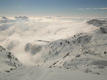 Peak of mountains in ski resort are sticking out from the low mist. Stock Image