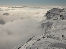 Peak of mountains in ski resort are sticking out from the low mist. Stock Photo