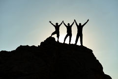 Peak reached a real success story. Three characters (climbers) seen in silhouette with  arms raised on top of mountain peak, a symbol of success and unity of Stock Images