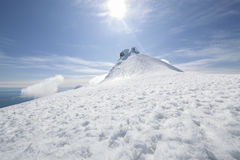 Peak of Snaefellsjokull. The picture shows the snow-capped peak of a mountain, two climbers can be seen on closer inspection stock photos