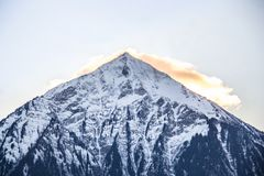 Peak of a snowy mountain on a lake in Switzerland royalty free stock photo