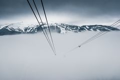 Peak to peak cable car at Whistler, Canada. Cable car wires dissapearing into fog Royalty Free Stock Photo