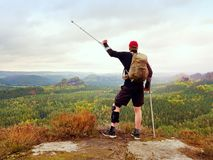 Peak triumph. Man with leg in knee cages and crutches for stabilization and walk support. Hiker use adjustable side panels to immobilize and support of hurt Stock Photography