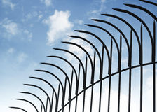 Peaked fence on blue sky stock photography