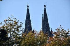Peaking Dom. Abstract angle of Köln Dom in the fall with the twin towers rising behind colorful trees Stock Photos