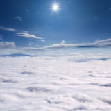 Peaks above the clouds against sun Stock Photography