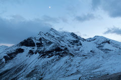 Peaks of Austrian alps and a moon in summer Royalty Free Stock Photos