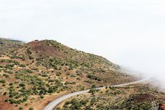 The Road Ends In the Clouds. The peaks covered in clouds, with the road disappearing in it royalty free stock image