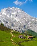 The peaks of Europe in which you can see some mountain shelters. An excursionist route and a meadow grass with mountains in the background Stock Images
