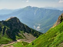 The peaks of a high mountain slope with cable car, in front of which is a valley with residential houses. Blue sky in the mountains on a summer day. Krasnaya stock photography