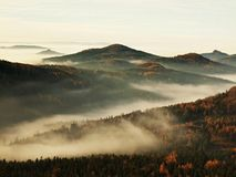 Peaks of hills and trees are sticking out from yellow and orange waves of mist. Royalty Free Stock Images
