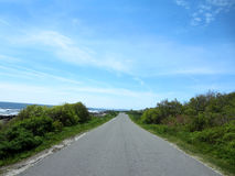 Peaks Island road way with granite rocky shoreline, trees and aw Royalty Free Stock Photos