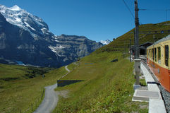 Peaks, meadow and train in Kleine Scheidegg in Switzerland Royalty Free Stock Photography