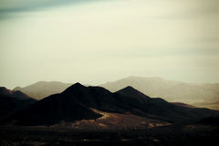 Peaks and mountain ranges in the desert. Top peaks and ranges of rough darker and brighter mountains in the Mojave Desert near Death Valley Junction stock photos