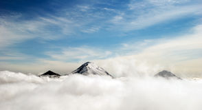 Peaks of mountains above the clouds Stock Photography
