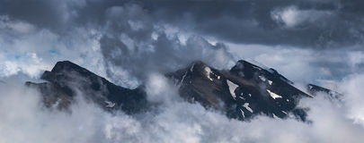 Peaks of ridge Abushura Akhuba jutting out from of cloud. Royalty Free Stock Photo