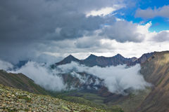 Peaks of rocky mountains in clouds and fog Royalty Free Stock Photo