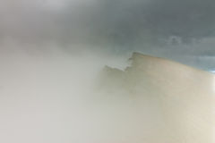 Peaks of rocky mountains in clouds and fog Stock Photos