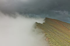 Peaks of rocky mountains in clouds and fog Royalty Free Stock Image