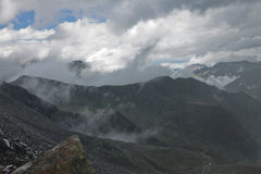 Peaks of rocky mountains in clouds and fog Stock Photo