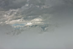 Peaks of rocky mountains in clouds and fog Stock Image