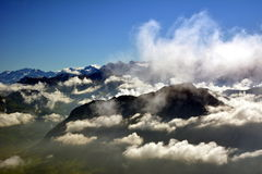 Peaks towering above the clouds Stock Photos