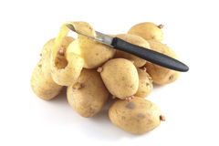 Pealing potatoes. On a white background Royalty Free Stock Images