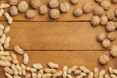 Peantus and walnuts on wood Royalty Free Stock Photography