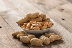 Peanut or arachis in white bowl on wood table. Peanut or arachis in white bowl on wood table Royalty Free Stock Photo