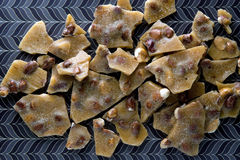 Peanut Brittle on brown pattern background Royalty Free Stock Images