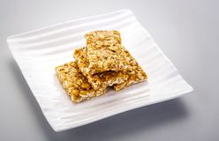 Peanut brittle or peanut chikki and roasted groundnuts. Peanut brittle or peanut chikki made of jaggery and peanuts and roasted groundnuts royalty free stock photography