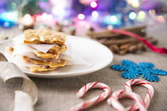 Peanut Brittle for Christmas. Festive scene with peanut brittle on a plate and candy canes and other Christmas decorations stock photos