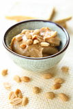 Peanut Butter. With whole nuts in glass bowl. There is excellent addition for sandwiches and desserts Stock Photo
