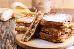 Peanut butter and banana french toasts. With powdered sugar on rustic wooden table Royalty Free Stock Images
