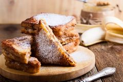 Peanut butter and banana french toasts. With powdered sugar on rustic wooden table Royalty Free Stock Photo