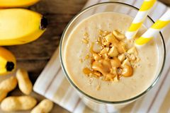Peanut-butter banana oat smoothie close up, downward view. Peanut butter banana oat smoothie with paper straws close up, downward view with cloth royalty free stock photography