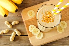 Peanut-butter banana oat smoothie with straws, on wood Royalty Free Stock Images