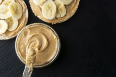 Peanut butter and banana on rice cakes, healthy, dietary food. Black background. Peanut butter and banana on rice cakes healthy, dietary food. Black background royalty free stock photo