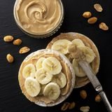 Peanut butter and banana on rice cakes, healthy, dietary food. Black background. Peanut butter and banana on rice cakes healthy, dietary food. Black background royalty free stock image