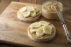 Peanut butter and banana on rice cakes, healthy, dietary food. Peanut butter and banana, rice cakes, healthy, dietary food. Wooden background snack breakfast stock image