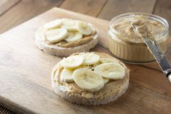 Peanut butter and banana on rice cakes, healthy, dietary food. Peanut butter and banana, rice cakes, healthy, dietary food. Wooden background snack breakfast stock images
