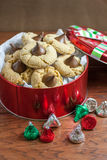 Peanut Butter Blossom Cookies. Preanut butter blossoms in a gift tin, highlighted with chocolate candies and and cookies on a wooden table Stock Photography
