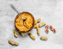 Peanut butter in the bowl. On a rustic background stock photography